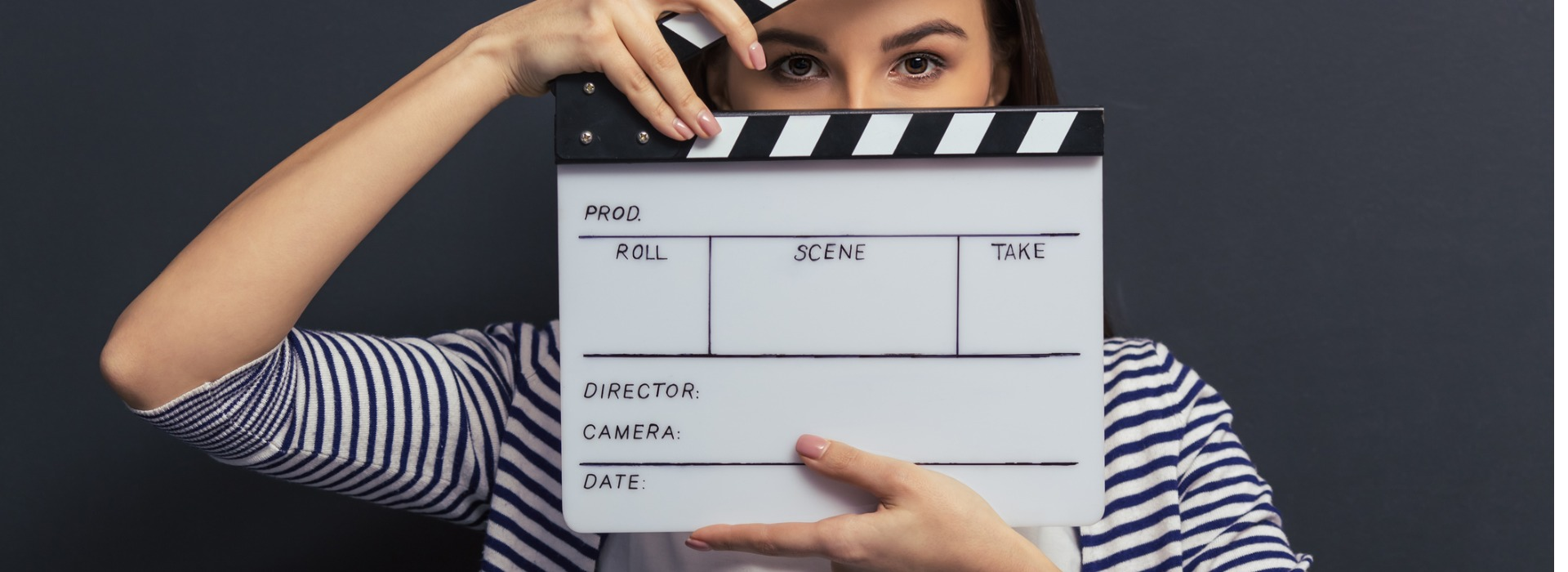 Girl with clapperboard in front of face